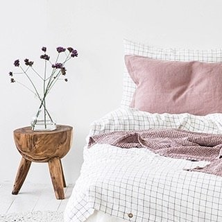 White and pink bedding with wooden night stand